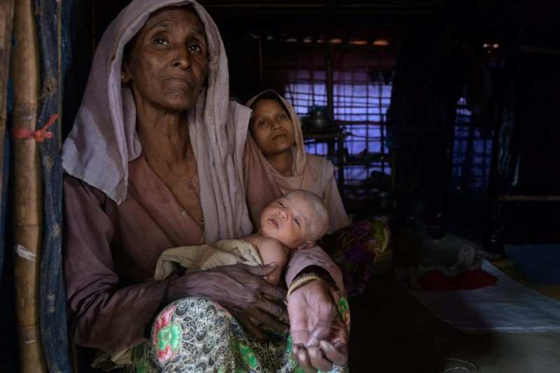 Rohingya refugee Setara (20, R) sits behind her 8-day-old baby, and her mother-in-law Sokhina Khatun (60, L) at the Thangkhali refugee camp near Cox's Bazar, southern Bangladesh, on Aug. 11, 2018. (AFP Photo)