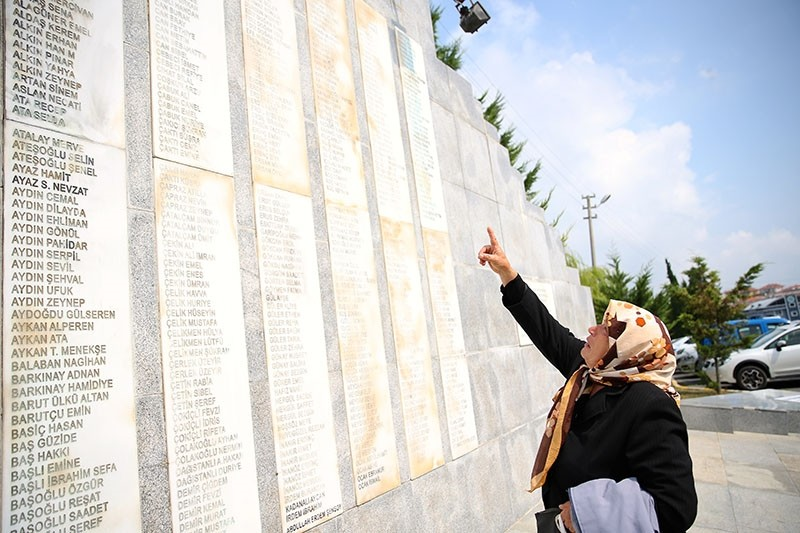 A woman searches for the name of her relative, who died in the earthquake, amid hundreds of names engraved on a Aug. 17 earthquake memorial in Sakarya, Turkey, Aug. 17, 2017. (AA Photo)