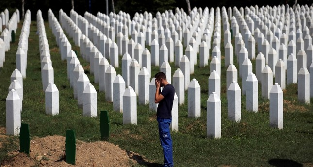 A man prays among gravestones at the memorial centre of Potocari near Srebrenica, 150 kms north east of Sarajevo, Bosnia, Tuesday, Aug. 14, 2018. (AP Photo)