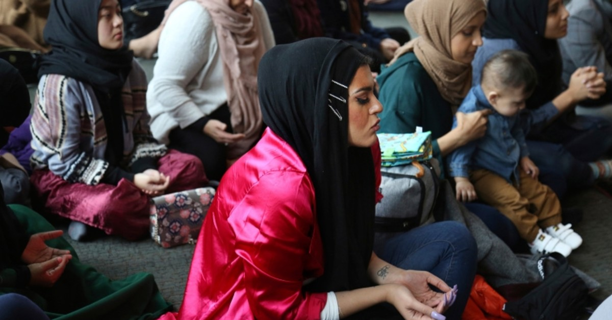 In this Dec. 27, 2019, photo, Amani Al-Khatahtbeh, center, sits near the back of the room at the Islamic Center of New York University during Friday prayers. (AP Photo)
