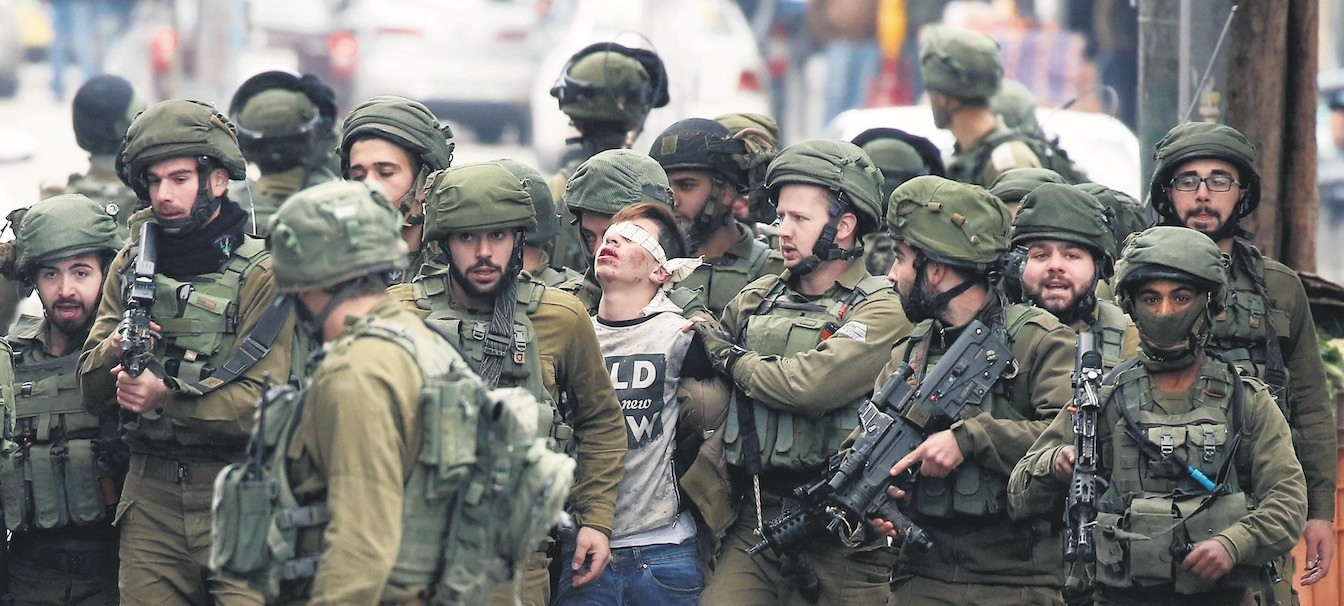 2017u2019s most symbolic photo is that of Fawzi al-Juneidi, the 16-year-old Palestinian boy, being detained by Israeli soldiers after his protests against Trump's decision on Jerusalem and Israeli state's occupation in his land, the West Bank, Dec. 7.
