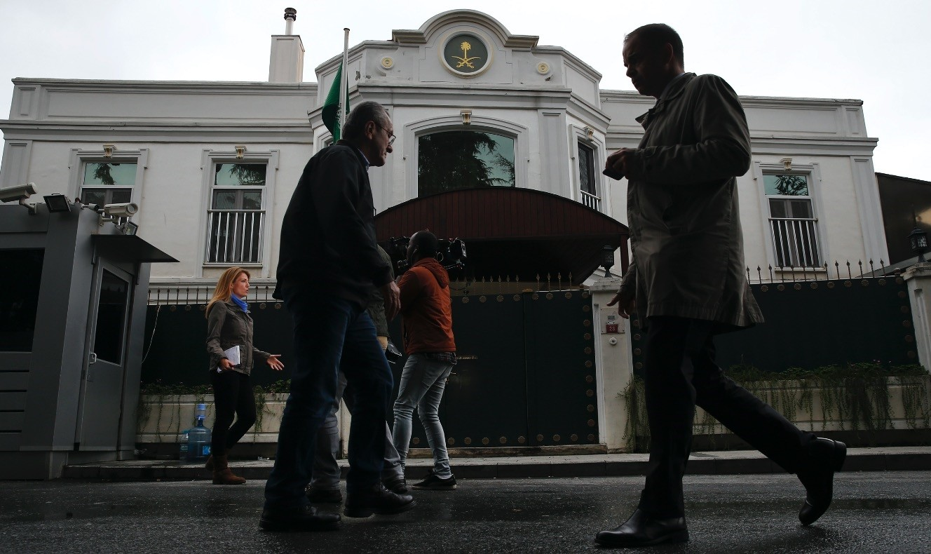 Pedestrians walk by as members of the media report from outside of Saudi Arabiau2019s consul generalu2019s residence in Istanbul, Oct. 18.