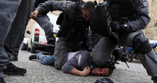 Israeli police officers detain a Palestinian protestor during scuffles outside the compound housing al-Aqsa Mosque in Jerusalem's Old City March 12, 2019. (Reuters Photo)
