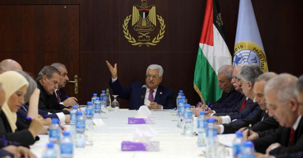 Palestinian President Mahmud Abbas (C) gestures during his meeting with the newly announced government in the Israeli-occupied West Bank town of Ramallah. (AFP Photo)