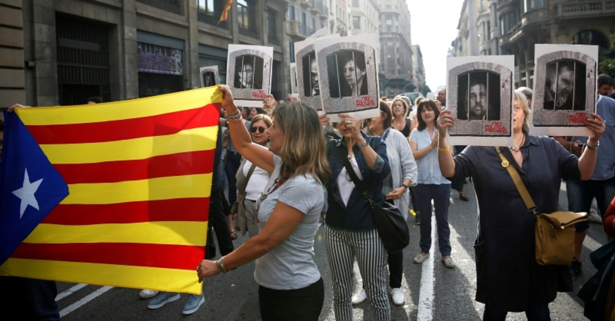 People holding an Estelada (Catalan separatist flag) and pictures of Catalan politicians as they walk through Via Laetana Avenue during a protest after a verdict in a trial over a banned independence referendum, in Barcelona, Oct. 14, 2019. (Reuters)