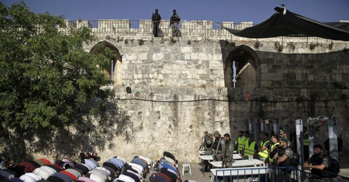 Israeli border police stand guard as Muslims pray outside the Al-Aqsa Mosque compound, Jerusalem. (AP Photo)