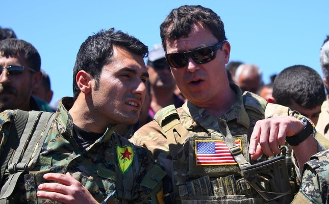 This file photo taken on April 25, 2017 shows a US officer, from the US-led coalition, speaking with a YPG terrorist at the site of Turkish airstrikes near northeastern Syrian Kurdish town of Derik, known as al-Malikiyah in Arabic, on April 25, 2017.