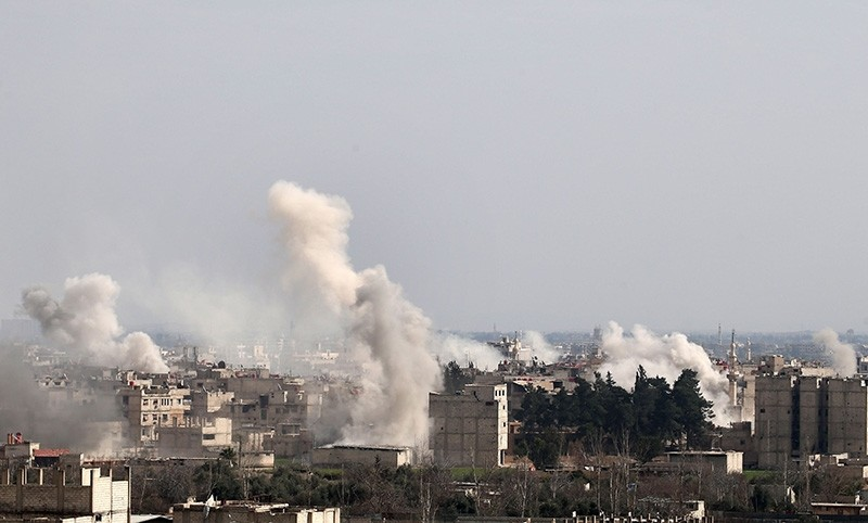 A picture taken on February 20, 2018 shows smoke plumes rising following a reported regime air strike in the opposition-held town of Hamouria, in the besieged Eastern Ghouta region on the outskirts of the capital Damascus. (AFP Photo)
