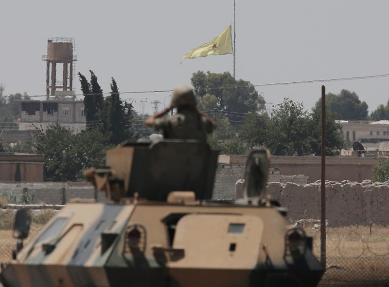 In this photo taken in Aku00e7akale, SE Turkey, a Turkish soldier on an armored personnel carrier watches as in the background a flag of the PKK-linked YPG, is raised across the border over the city of Tal Abyad, Syria, Tuesday, June 16, 2015. (AP Photo)