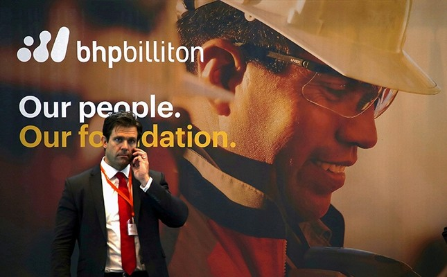 An official stands in front of a sign for mining company BHP Billiton outside the Perth Convention Centre, where their annual general meeting was being held in Perth, Western Australia, November 19, 2015.(Reuters Photo)