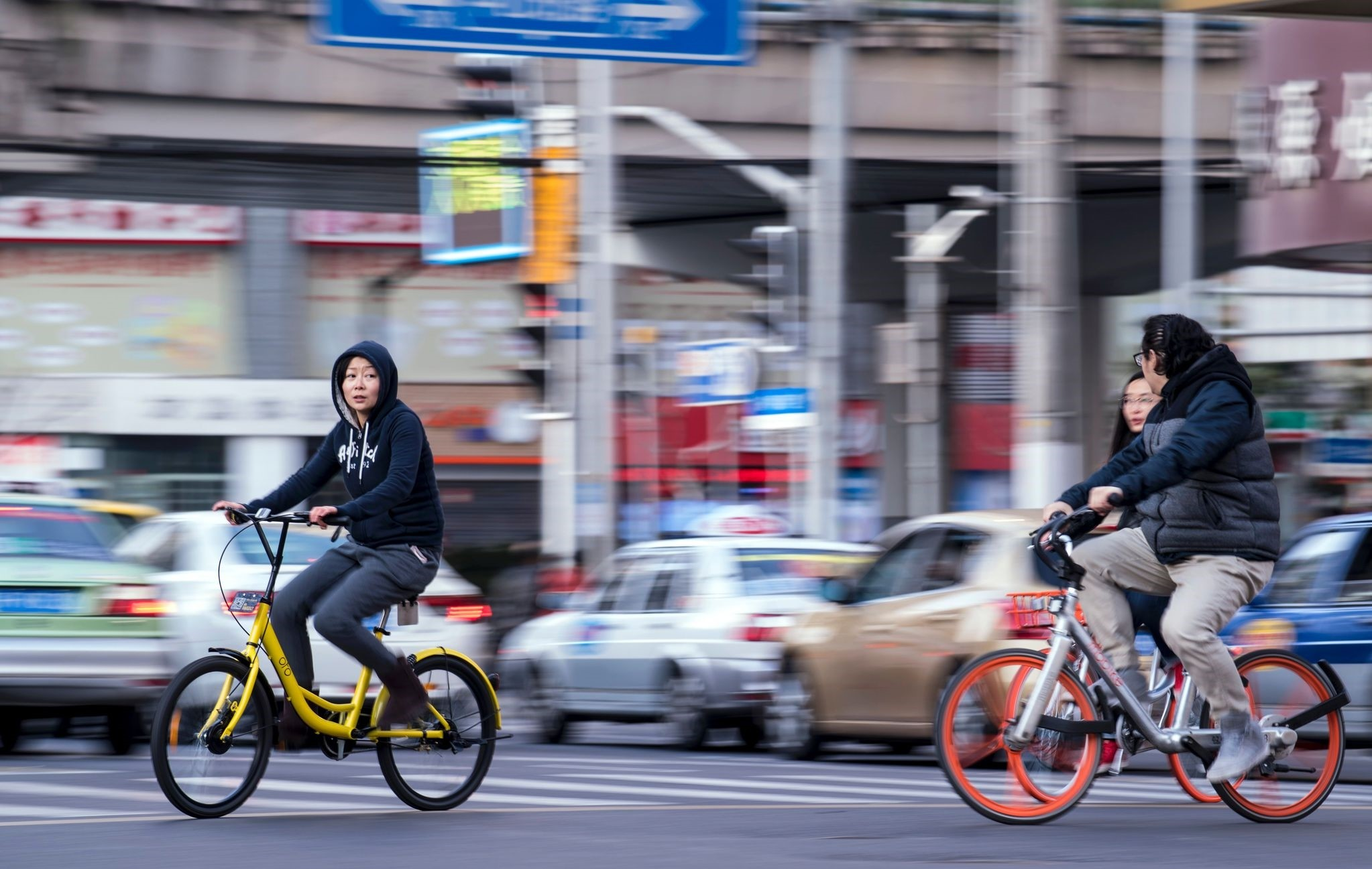 People ride bicycles of Ofo (L) and Mobike sharing companies on a street in Shanghai.