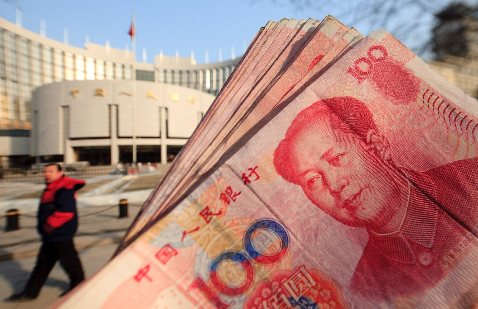Renminbi banknotes and the headquarters of the Peopleu2019s Bank of China (PBOC) in central Beijing.