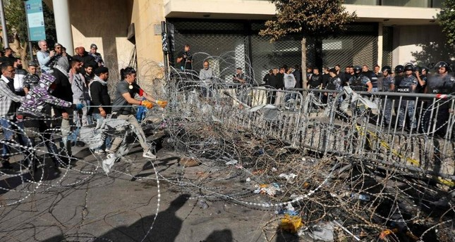 Lebanese protesters use cables to bring down security barriers along a road leading to the parliament headquarters, Beirut, Nov. 19, 2019. (AFP Photo)