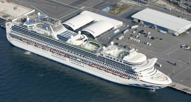 The U.S.-operated Diamond Princess is anchored as emergency vehicles stand by at Yokohama Port, near Tokyo, Wednesday, Feb. 12, 2020. Kyodo News via AP