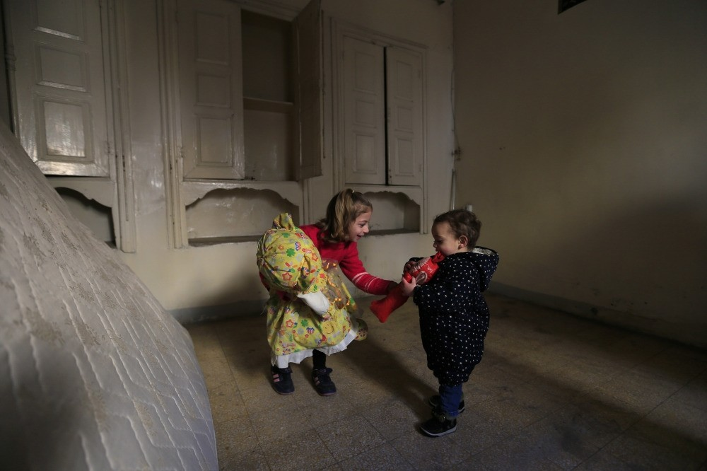 Shurouq, 6, left, gives her brother Mustafa, 2, a toy as she holds a doll that she left at her home, after she returned with her family to eastern Aleppo.