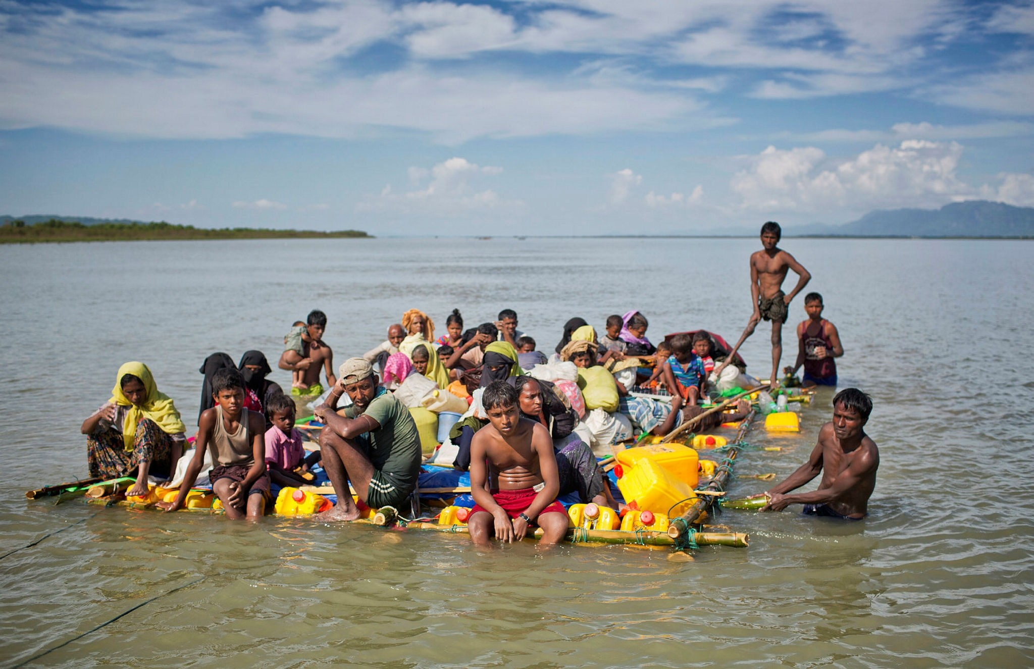 Rohingya refugees travel on a raft made with plastic containers on which they crossed the Naf River from Myanmar to Bangladesh.
