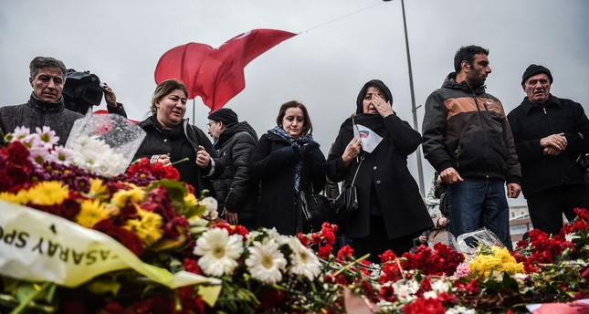 People lay flowers for the victims of the Dec. 10 blasts outside Beşiktaş Vodafone Arena football stadium Tuesday.