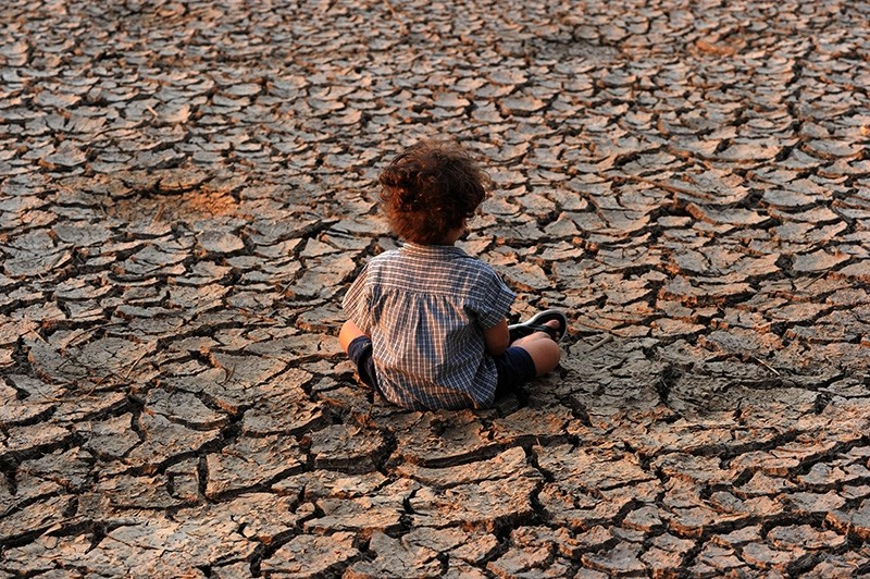 This file photo taken on April 22, 2016 shows a child sitting on dry soil in an area affected by a drought on Earth Day in the southern outskirts of Tegucigalpa. (AFP Photo)