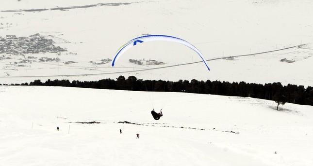 A paraglider flies over skiers at the Yalnızçam Ski Center in Ardahan, Turkey.