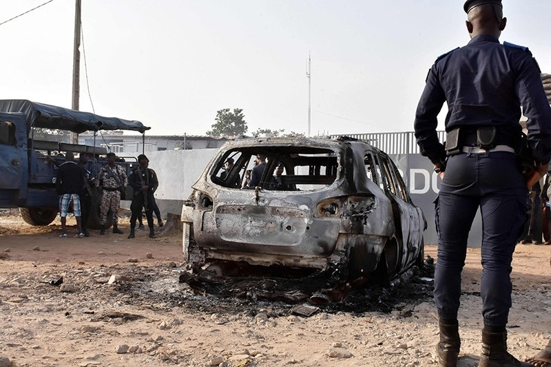 A gendarme stands in front of the wreckage of a burnt car, on Jan. 10, 2018 in front of the CCDO elite military unit center, a day after gunshots and heavy weapons fire erupted between rival factions within Ivory Coastu2019s army. (Reuters Photo)