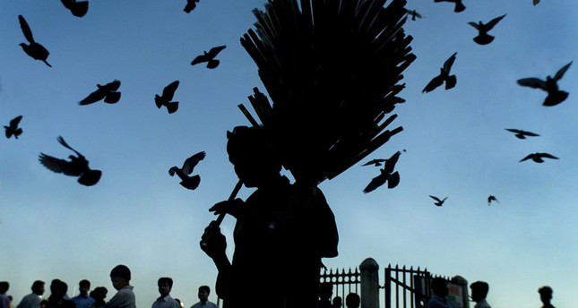 An Indian Muslim flute seller plays one of his wares to attract buyers in Bombay, April 18, 2002.