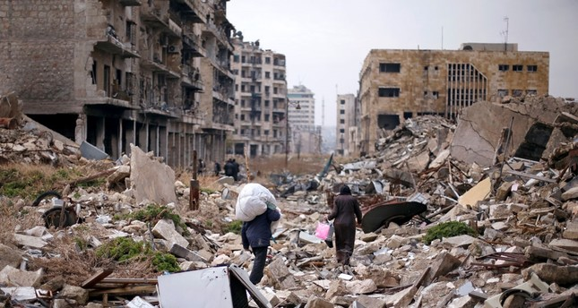 People walk amid the rubble as they carry belongings that they collected from their houses before they leave Aleppo, Syria Dec. 17, 2016.
