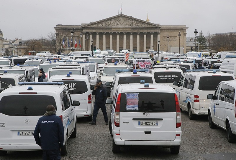Ambulance workers block the bridge leading the National Assembly, background, in Paris, Monday, Dec. 3, 2018. (AP Photo)
