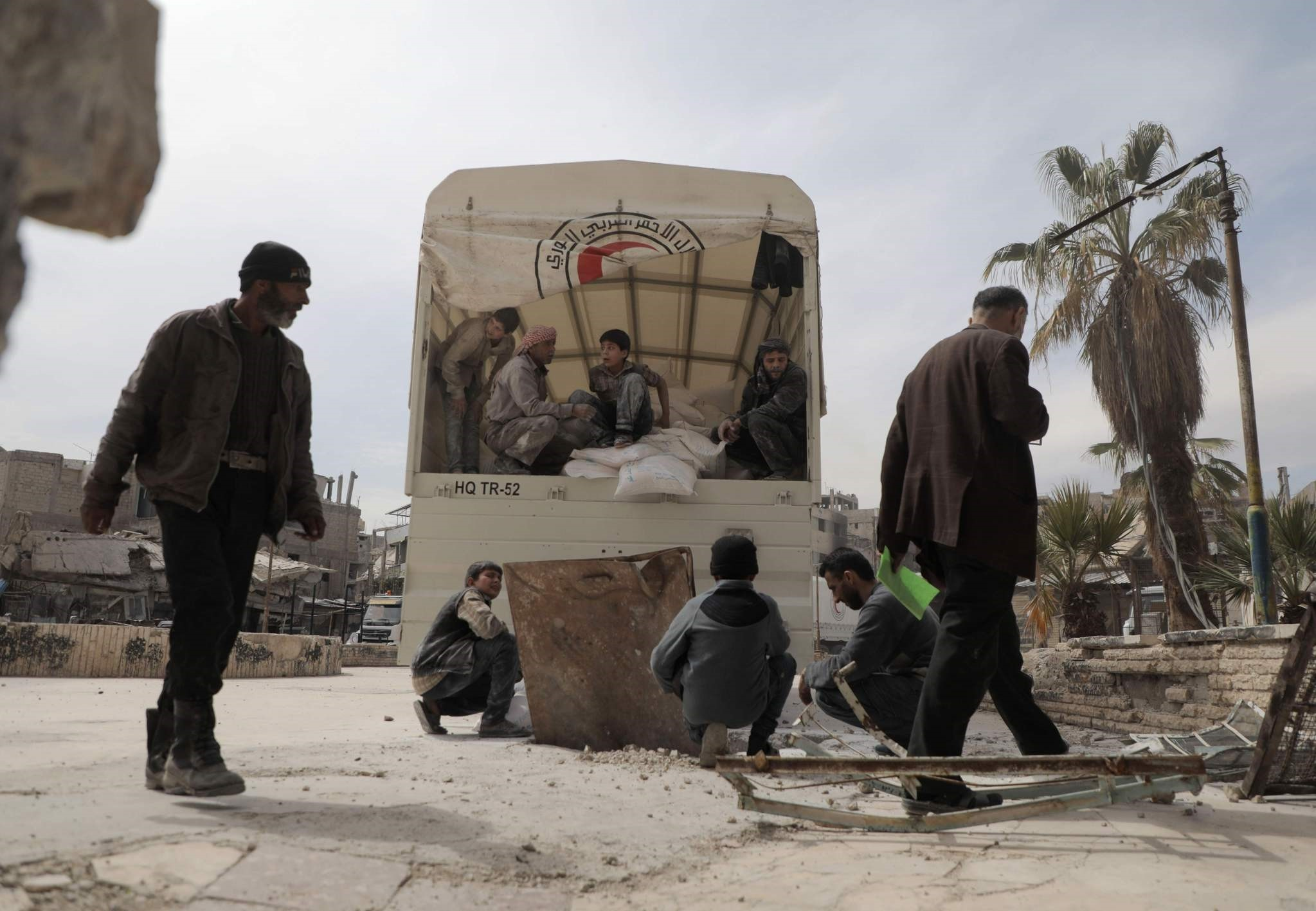 Syrians offload sacks of flour into an underground storage space after a humanitarian convoy carrying food aid arrived in the opposition-held town of Douma, in Eastern Ghouta. (AFP Photo)