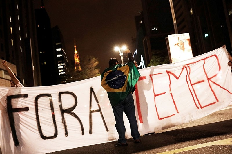 A demonstrator draped with a Brazilian Flag is pictured in front a banner reading  ,Temer out,  during a protest against Brazil's President Michel Temer in Sao Paulo, Brazil, May 17, 2017. (Reuters Photo)