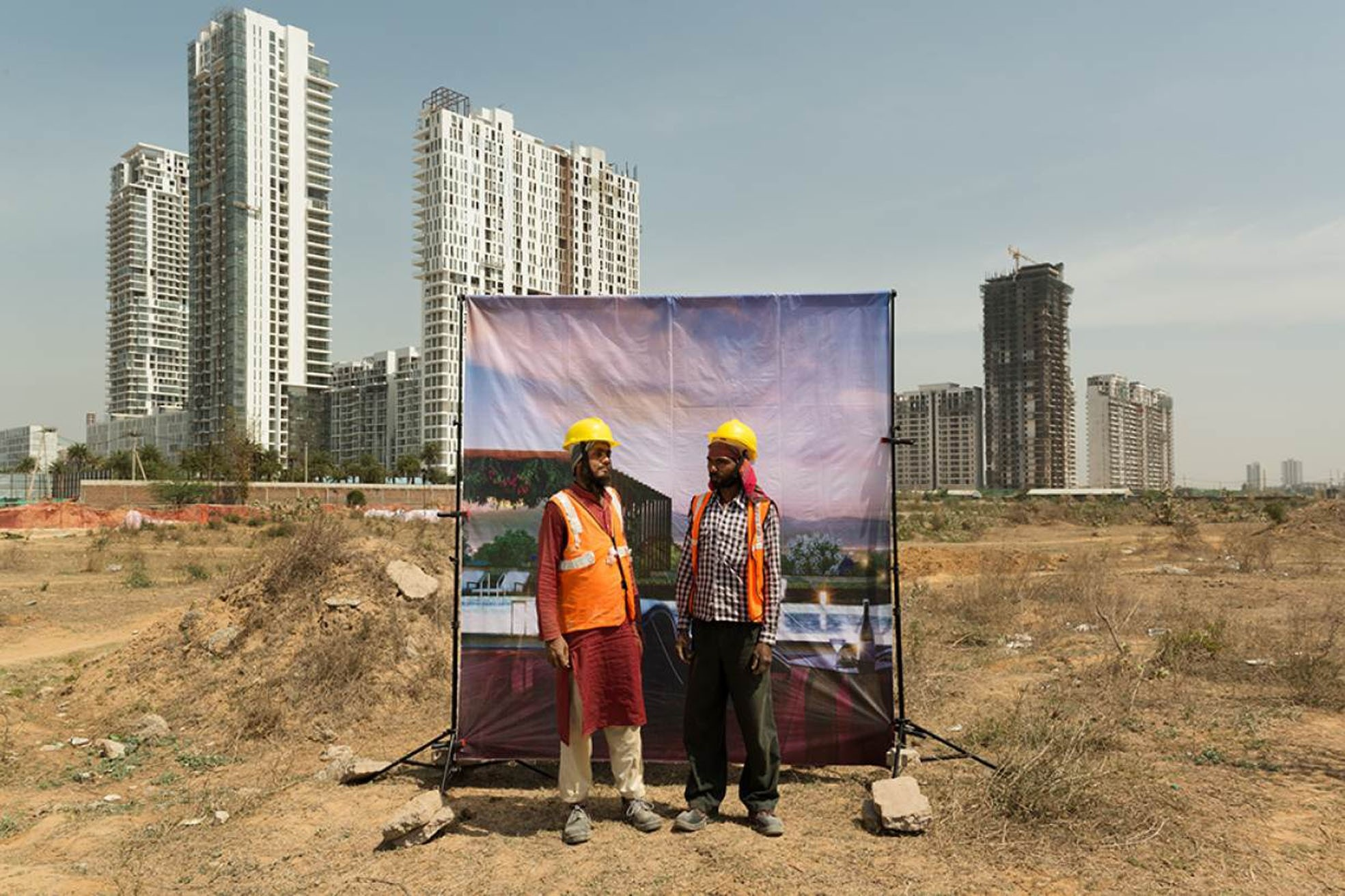 Construction workers pose against large, glossy advertisements for luxury developments, with construction sites looming behind them.