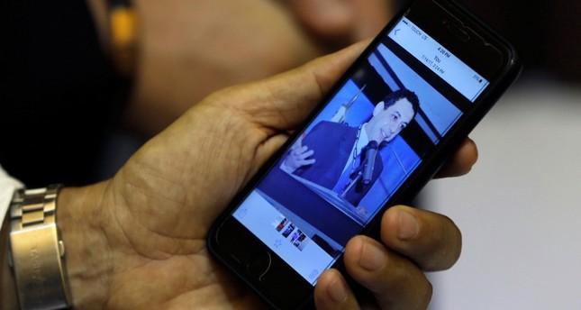 زياد زكا شقيق نزار زكا المسجون في إيران، يظهر صورة لأخيه على هاتفه الخلوي (AP)