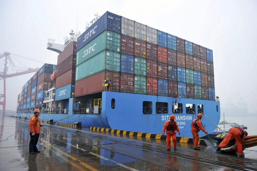 Workers moor a container ship at a port in Qingdao in east China's Shandong province, Jan. 11, 2019.