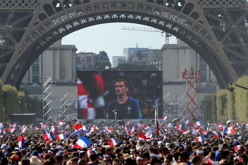 In this Sunday, July 15, 2018 file photo, people watch a giant screen during the World Cup final between France and Croatia, on the Champ de Mars next to the Eiffel Tower in Paris. (AP Photo)